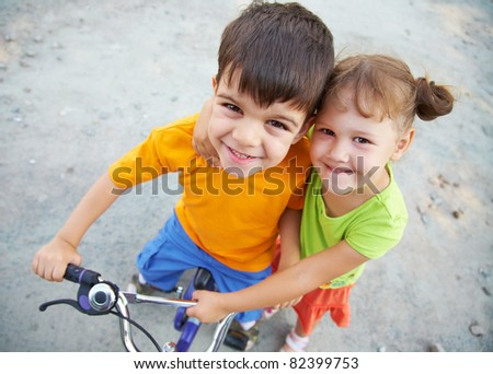 Portrait of cheerful girl and  fun boy with bike on the grey asphalt - stock photo