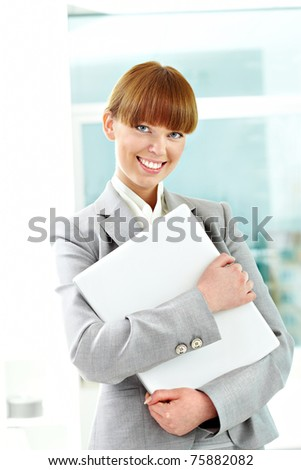 Portrait of cheerful girl holding laptop and looking at camera - stock photo