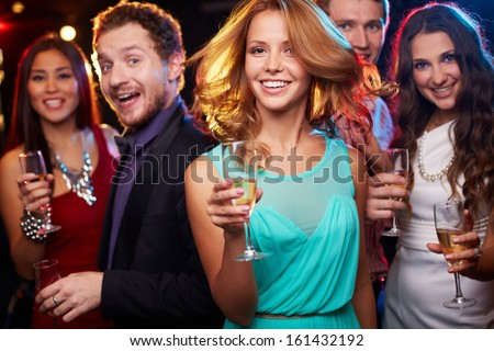 Portrait of cheerful girl with champagne flute dancing at party on background of her friends - stock photo