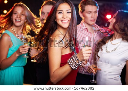 Portrait of cheerful girl with champagne flute dancing at party while smiling at camera - stock photo