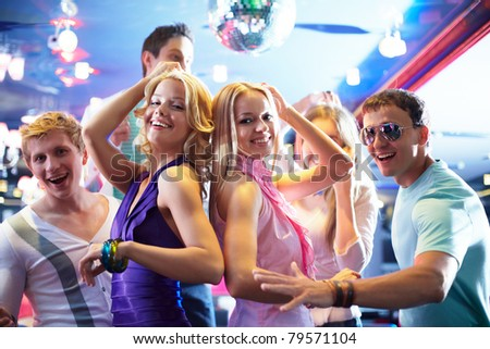 Portrait of cheerful girls dancing at party with happy friends near by - stock photo