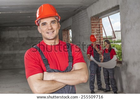 Portrait of cheerful handsome young adult  industrial engineer wear plastic helmet uniform overall and red cotton shirt look at camera against two worker with blueprint paper plan near window frame  - stock photo
