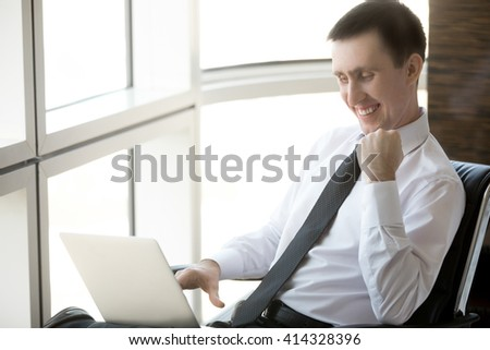 Portrait of cheerful handsome young business man sitting in his office using technology. Happy corporate businessperson working on laptop computer and celebrating success - stock photo