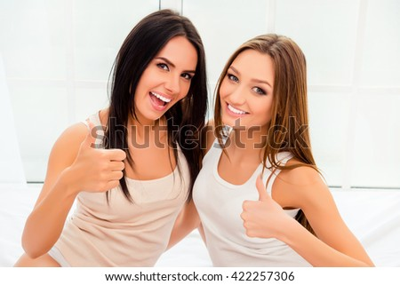 Portrait of cheerful happy sisters showing thumbs up - stock photo