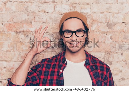 Portrait of cheerful hipster man in glasses gesturing ok
