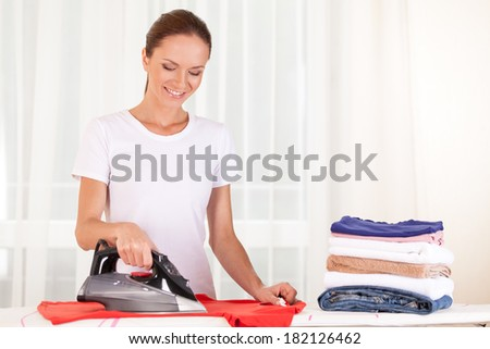 Portrait of cheerful housewife ironing clothes. waist up housewife standing in bedroom and ironing - stock photo