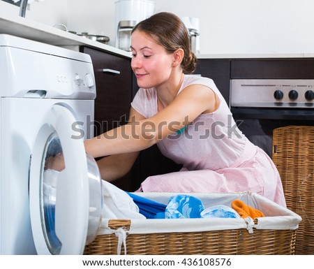 Portrait of cheerful housewife loading washing machine in kitchen