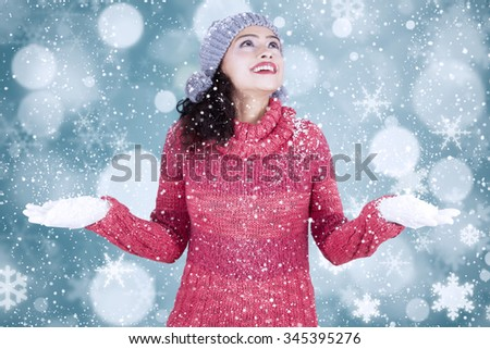 Portrait of cheerful indian woman wearing warm clothes while playing snow with bokeh background - stock photo