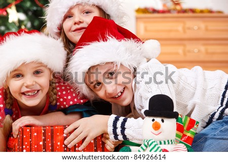 Portrait of cheerful kids in Christmas hats - stock photo