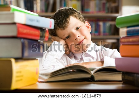 Portrait of cheerful lad sitting in library before book and looking at camera with smile