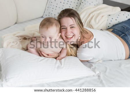 Portrait of cheerful laughing mother relaxing on bed with her 9 months old baby boy