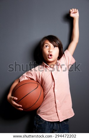 portrait of cheerful little boy raised his hand and holding a basketball with dark background - stock photo