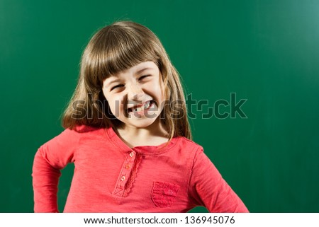 Portrait of cheerful little girl smiling in front of blackboard,Cheerful little girl - stock photo