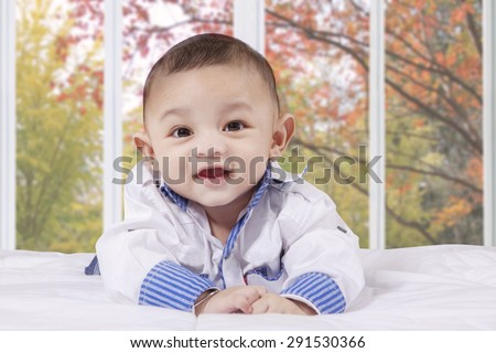 Portrait of cheerful male baby playing on the bed and laughing at the camera, shot at home - stock photo