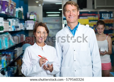 Portrait of cheerful man and woman pharmacists in white coat in pharmacy