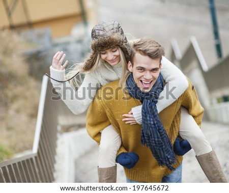 Portrait of cheerful man piggybacking woman on stairway - stock photo