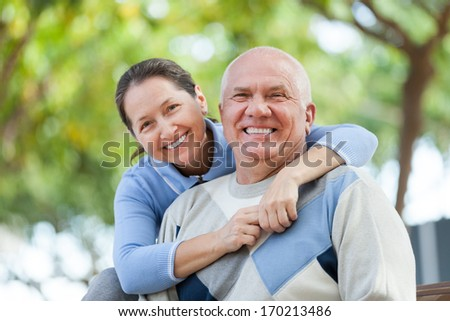 Portrait of cheerful mature couple in sweaters at autumn park - stock photo