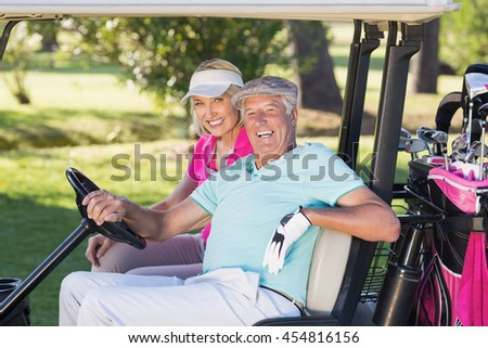 Portrait of cheerful mature golfer couple sitting in golf buggy - stock photo