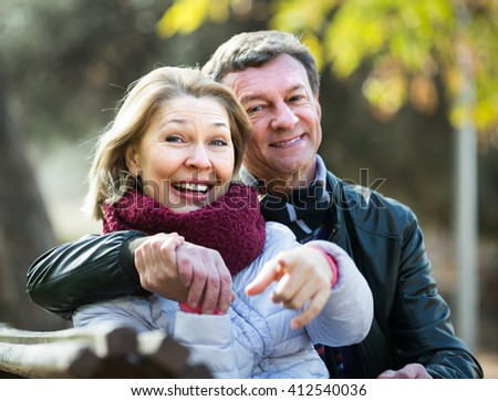 Portrait of cheerful mature spouses enjoying spending time outdoors at spring. Focus on woman - stock photo