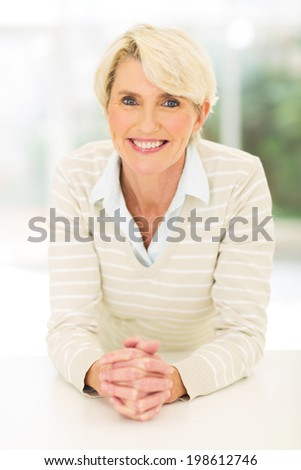 portrait of cheerful mid age woman relaxing at home - stock photo
