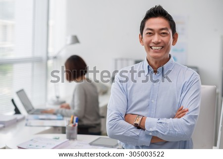 Portrait of cheerful middle-aged businessman standing in the office - stock photo