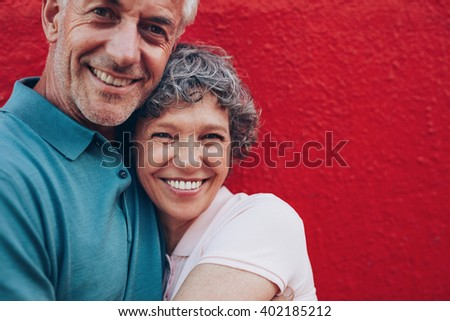 Portrait of cheerful middle aged couple embracing each other against red background. Mature man and woman together against red wall. - stock photo