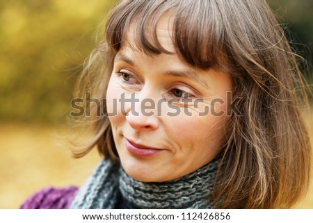 Portrait of cheerful middle aged woman in an autumn park - stock photo