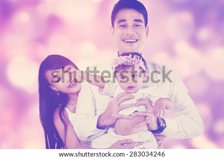 Portrait of cheerful parents and their female baby smiling at the camera, shot with a light glitter background - stock photo
