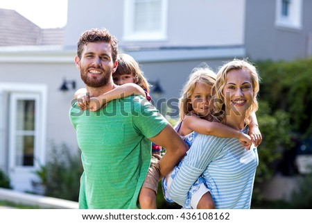 Portrait of cheerful parents piggy-backing children against house - stock photo