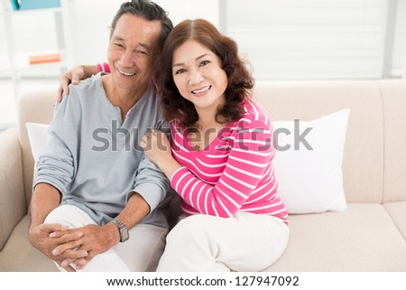 Portrait of cheerful pensioners enjoying their home life - stock photo