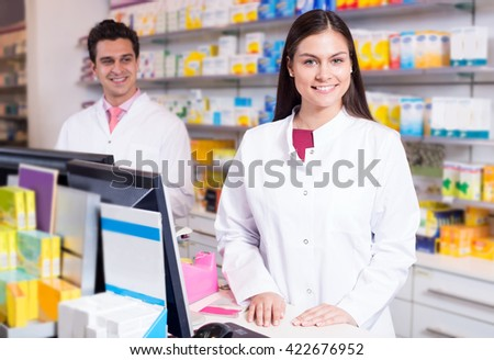 Portrait of cheerful pharmacist and assistant working at farmacy reception