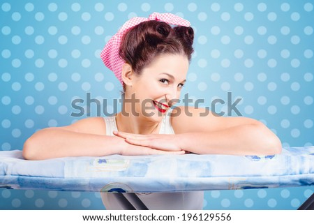Portrait of cheerful pinup housewife with glamorous 60s hairstyle and make up resting on clothes ironing board. Blue polka dots background - stock photo