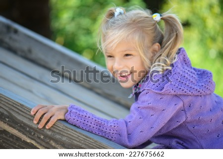 portrait of cheerful, pretty little girl with two tails was leaning on railing on background of summer park - stock photo