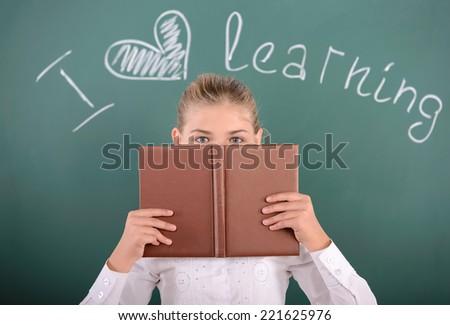 Portrait of cheerful school girl standing near blackboard - stock photo