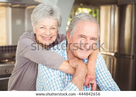 Portrait of cheerful senior couple embracing in kitchen at home - stock photo