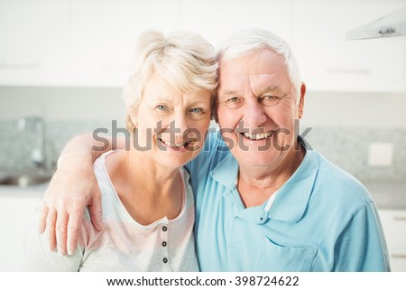 Portrait of cheerful senior couple in kitchen at home - stock photo