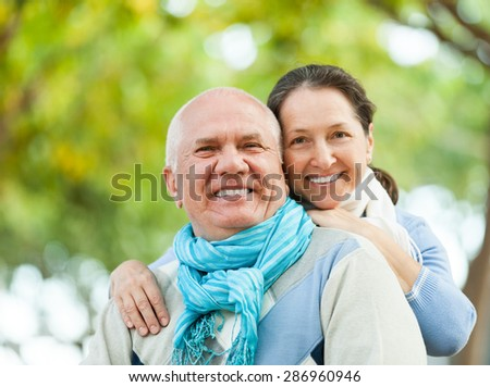 Portrait of cheerful senior couple together in autumn park - stock photo