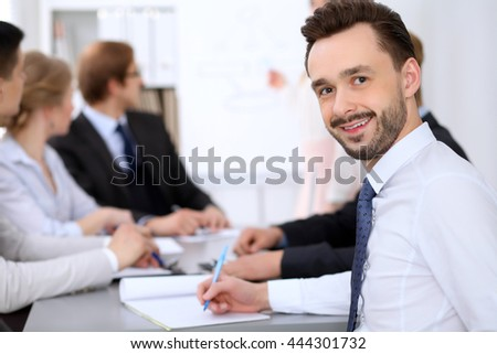 Portrait of cheerful smiling business man  against a group of business people at a meeting. - stock photo