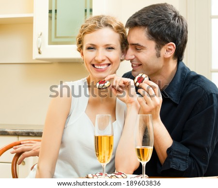 Portrait of cheerful smiling couple with champagne, indoors