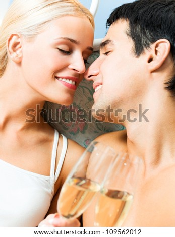 Portrait of cheerful smiling couple with glasses of champagne, indoors - stock photo