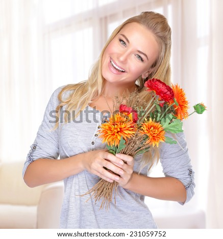 Portrait of cheerful smiling female with flowers bouquet in hands, spending autumn holiday at home, enjoying cute present  - stock photo