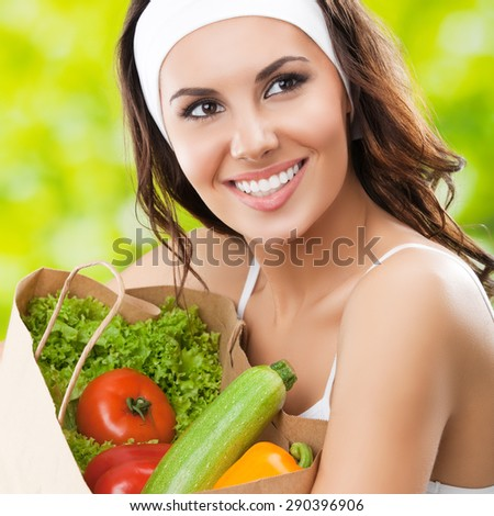 Portrait of cheerful smiling young beautiful brunette woman in fitness wear holding grocery shopping bag with healthy vegetarian raw food, outdoor. Healthy lifestyle, beauty and dieting concept. - stock photo
