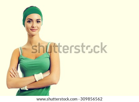 Portrait of cheerful smiling young brunette woman in green fitness wear, with blank copyspace area for slogan or text - stock photo
