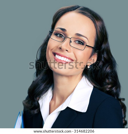 Portrait of cheerful smiling young businesswoman in black suit and glasses - stock photo