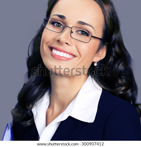 Portrait of cheerful smiling young businesswoman in black suit and glasses, posing at studio, over violet background - stock photo