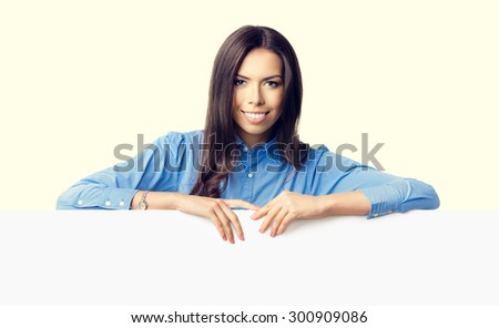Portrait of cheerful smiling young businesswoman showing blank signboard with copyspace for text or slogan message - stock photo