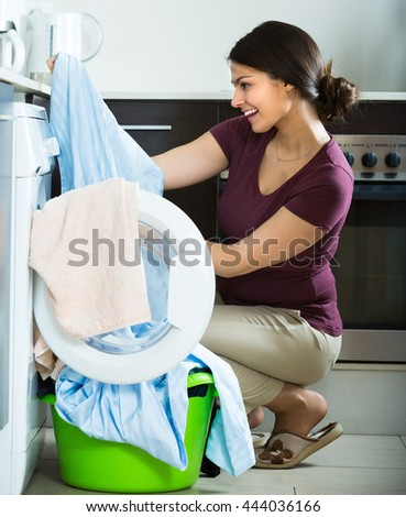 Portrait of cheerful smiling young housewife with washed linen near washing machine