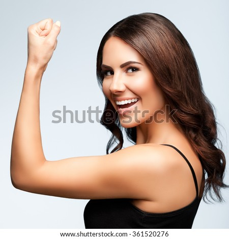 Portrait of cheerful smiling young woman happy gesturing, over bright grey background, square composition - stock photo