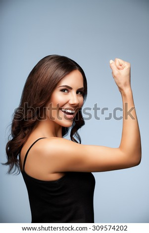 Portrait of cheerful smiling young woman happy gesturing, over grey background - stock photo