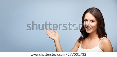 Portrait of cheerful smiling young woman in white casual clothing showing copyspace or something, over grey background - stock photo